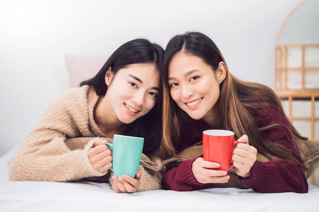 Amante lésbica dos pares das mulheres asiáticas bonitas novas que guarda o copo de café na sala da cama em casa.