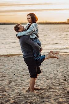 Amantes alegres se abraçam na praia. um encontro romântico ao pôr do sol.