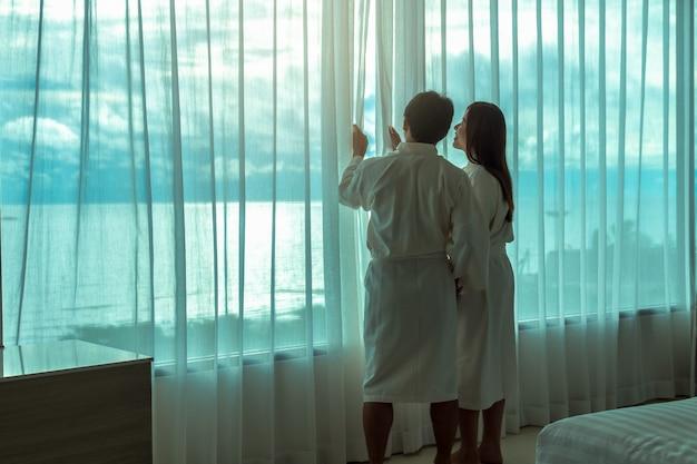 Amantes asiáticos em roupão de banho abertura e passeios a praia do mar ao acordar