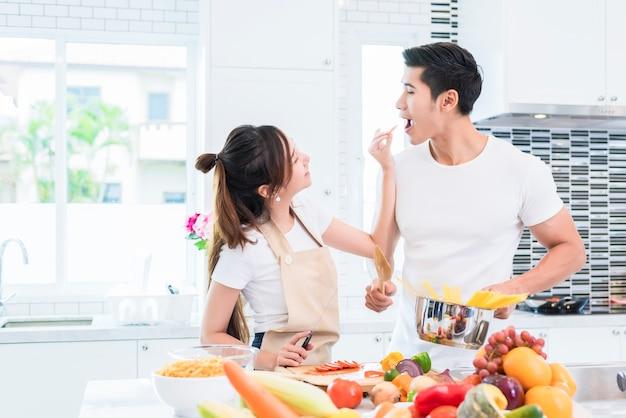 Amantes asiáticos que alimentam frutas e alimentos entre si