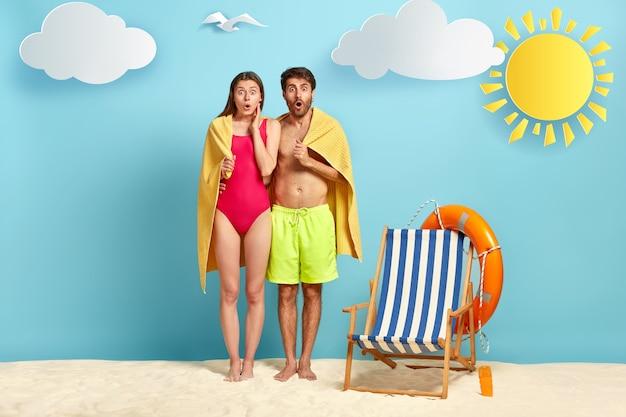 Amantes aterrorizados ficam próximos, cobertos com uma toalha macia, ficam em uma praia tropical, olham fixamente com os olhos bem abertos, viajam em lua de mel