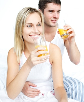 Amantes bebendo suco de laranja na cama