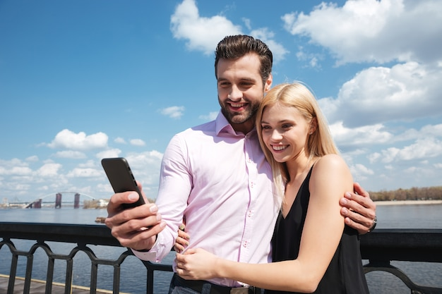 Amantes bonitos usando smartphone