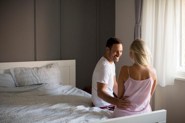 Amantes carinhosos abraçando na cama em casa