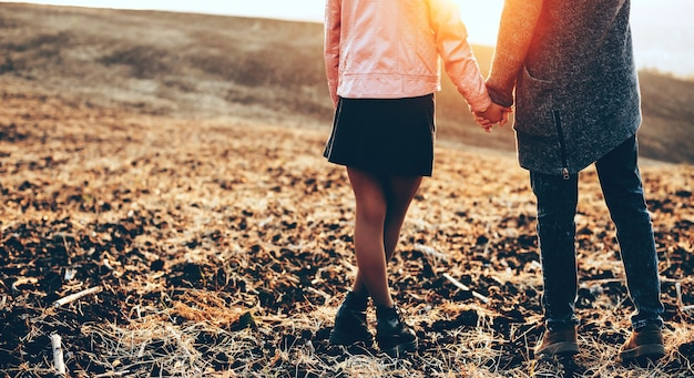 Amantes caucasianos posando de mãos dadas em um campo durante um pôr do sol de outono