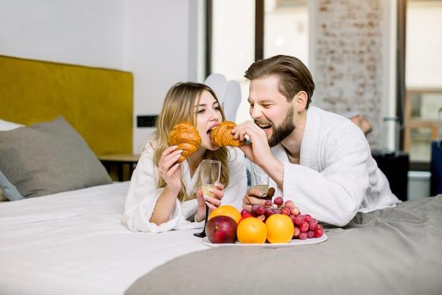 Amantes comemorando um noivado ou lua de mel com frutas frescas, croissants e champanhe na cama