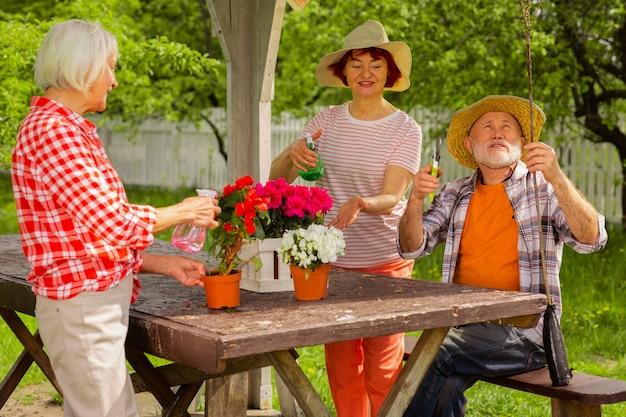Amantes da natureza. homem aposentado e duas mulheres cuidando de flores sentados juntos