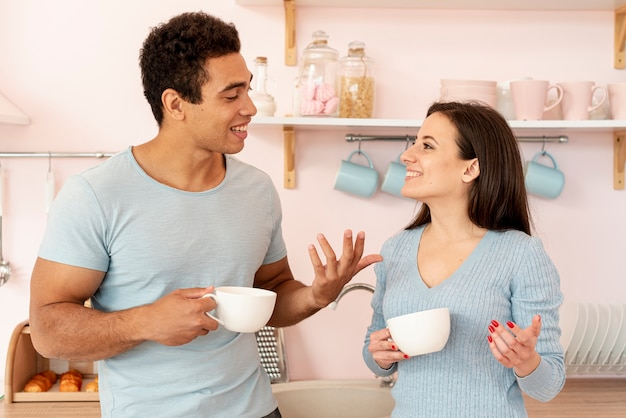 Amantes de tiro médio falando na cozinha