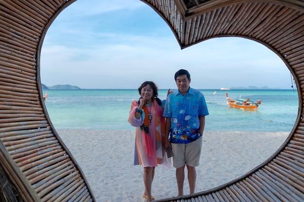 Amantes do casal asiático idoso feliz em pé na praia atrás da moldura de um coração de madeira.