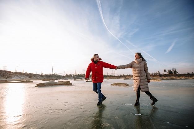 Amantes em jaquetas andam no gelo de poços de areia