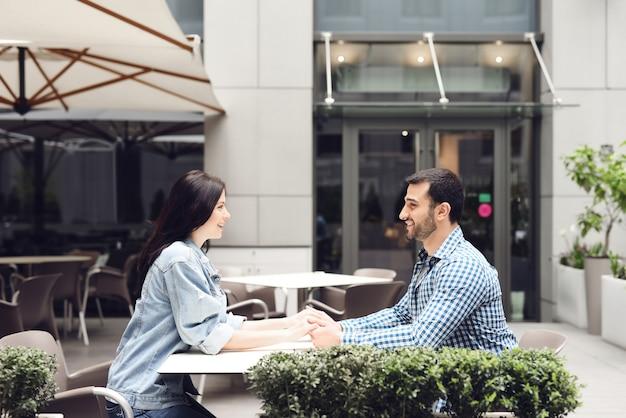 Amantes entusiasmados homem e mulher no café ao ar livre.