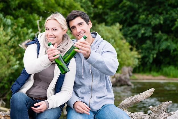 Amantes felizes em férias sentados à beira-mar em um baú tilintando garrafas de cerveja