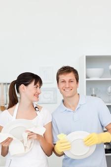 Amantes lavando pratos juntos