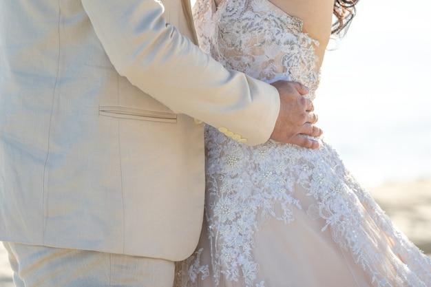 Amantes, noiva e noivo em ação amorosa, abraçados e ao lado da praia
