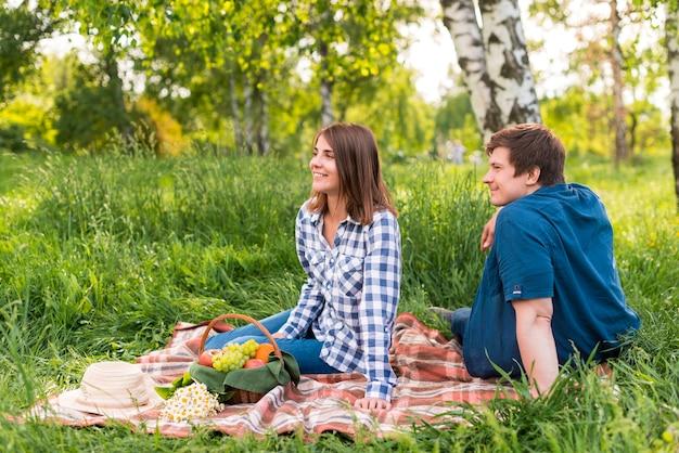 Amantes novos que sentam-se no cobertor na floresta do vidoeiro