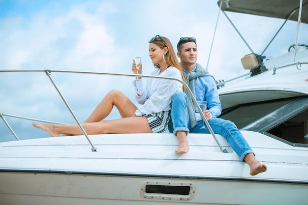 Amantes que passam o tempo feliz em um iate no mar. honeymood de luxo em um barco marítimo. conceito de férias, viagens, mar, amizade e pessoas. casal sorridente, sentado e conversando no convés do iate