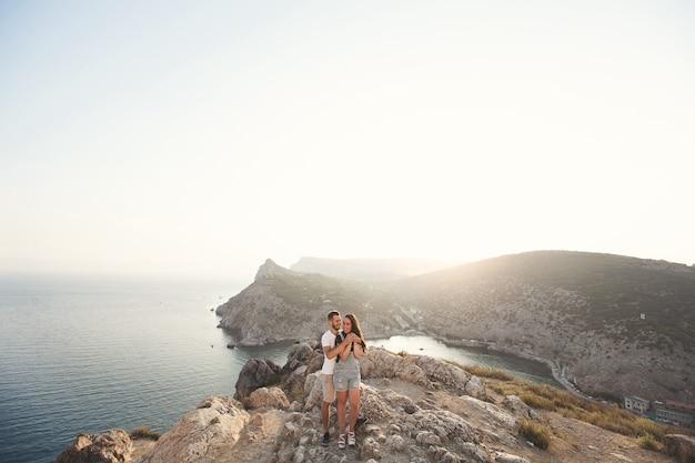 Amantes, rapaz e rapariga, à beira do penhasco contra o pano de fundo das montanhas e do oceano.