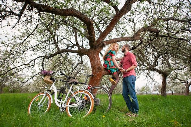 Amantes românticos perto da árvore e bicicletas no jardim primavera