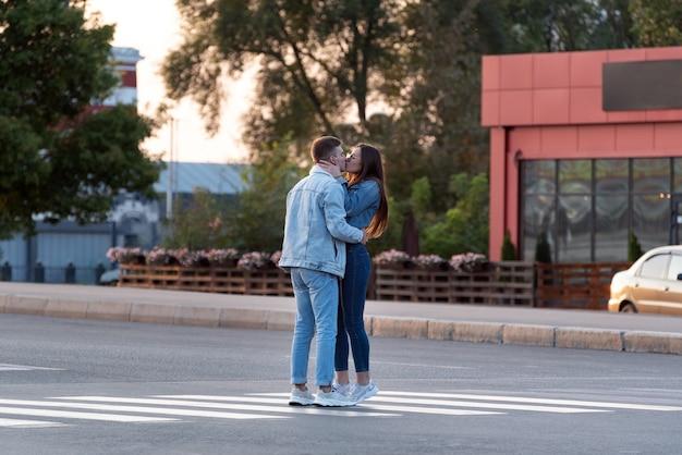 Amantes se beijam no meio da rua sob os raios do sol poente.