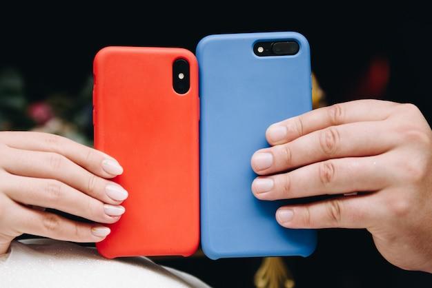 Amantes segurando dois telefones, azuis e vermelhos, para dia dos namorados em 14 de fevereiro