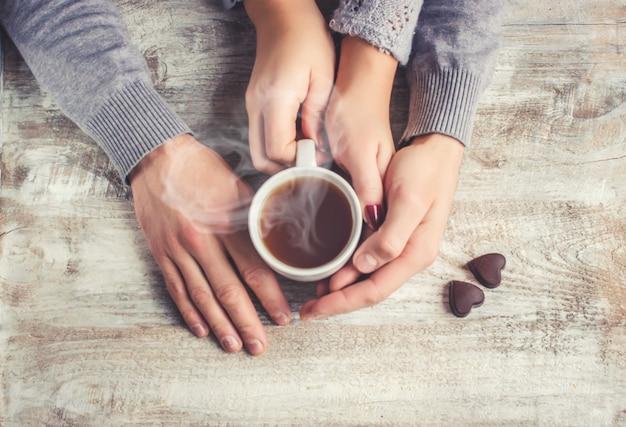Amantes segurando juntos uma xícara de chá. foco seletivo.