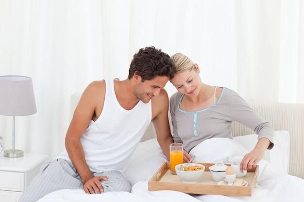 Amantes tomando café da manhã na cama