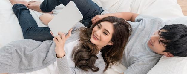Amantes usando o tablet digital em casa moderna
