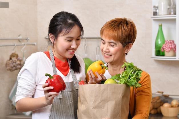Amar a família asiática de mãe e filha cozinhando na cozinha, fazendo alimentos saudáveis e segurando a sacola de compras com legumes juntos, sentindo-se divertido