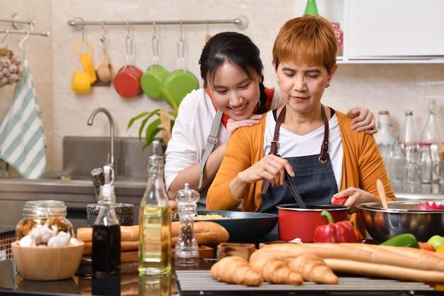 Amar a família de mãe e filha cozinhando na cozinha, fazendo alimentos saudáveis juntos, sentindo-se divertido