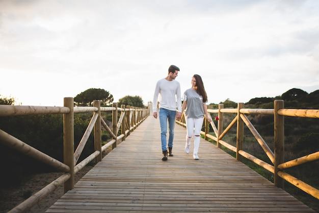 Amar casal andando em uma ponte pela mão