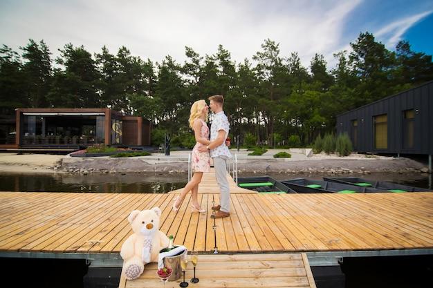 Amar o jovem casal beijos em um píer de madeira. história de amor no cais