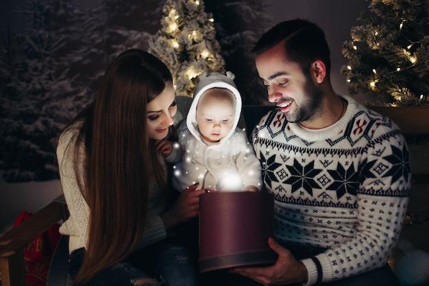 Amar os pais felizes com o bebê olhando para dentro do presente de natal