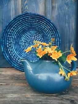 Amarelas flores silvestres em panela de barro azul