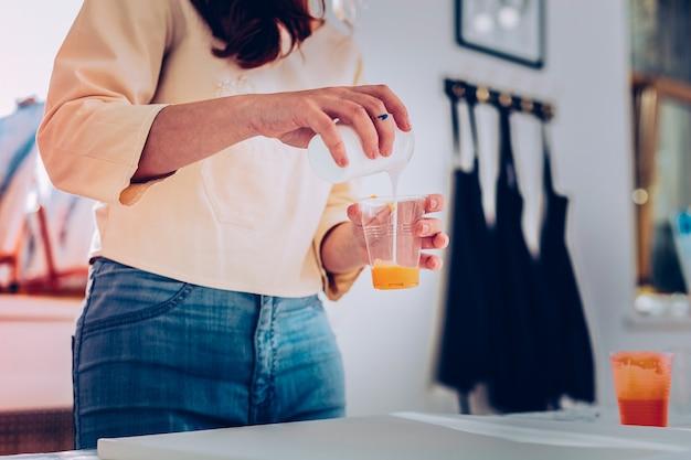 Amarelo e branco. jovem artista promissora vestindo jeans misturando aquarela com aquarela branca