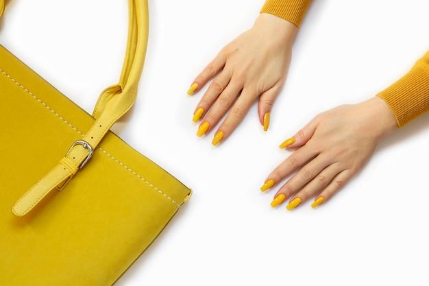 Amarelo elegante na bolsa e na manicure da menina.