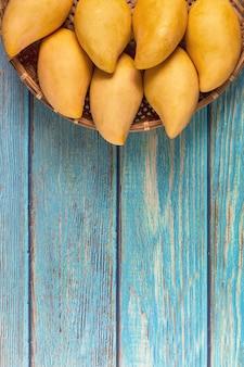 Amarelo fresh mangos 0n blue wood table. fruta tropical da manga. mangas. conceito de verão.