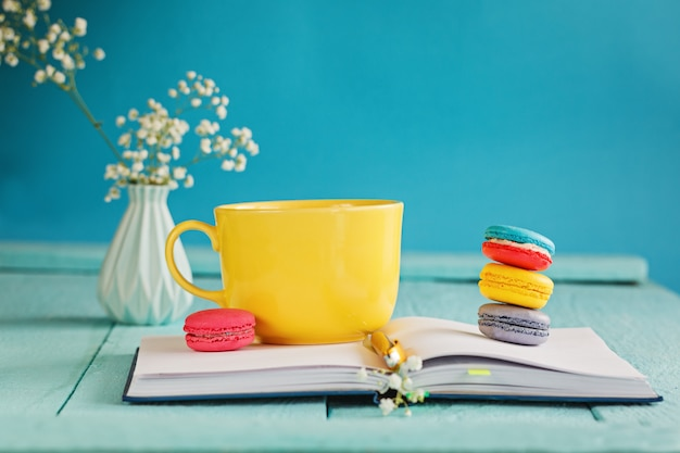 Amarelo grande xícara de chá com flores e biscoitos e notebook em azul