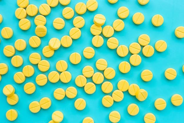 Amarelos comprimidos de paracetamol sobre fundo azul.