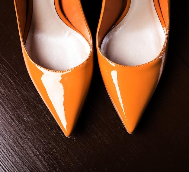 Amarelos sapatos femininos na superfície de madeira escura.