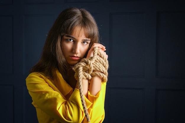 Amarrado com corda jovem mulher amarrada mãos mulher em cativeiro
