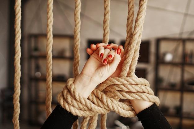 Amarrado com uma corda de mãos femininas. lindas mãos com unhas vermelhas. conceito de sexo ou violência