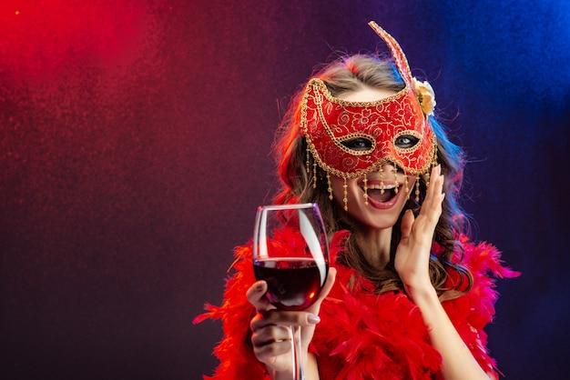 Amasing mulher em uma máscara de carnaval vermelho e boa com um copo de vinho.