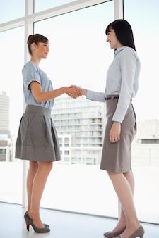 Ambas as mulheres sorriem enquanto apertam as mãos
