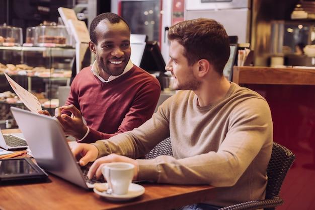 Ambiciosos habilidosos dois colegas trabalhando em um laptop enquanto estão sentados em um café e se comunicando