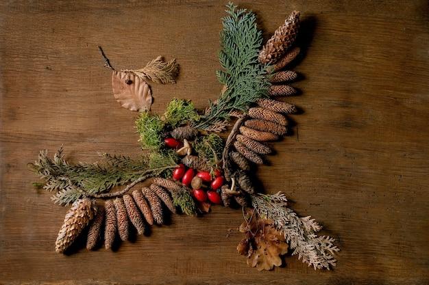 Ambiente de conto de fadas forma de pássaro voador outonal mágico de folhas de outono, musgo, cones de abeto sobre fundo de madeira. design de tendência de cartão postal ou papel de parede