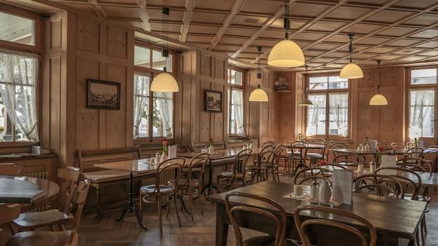 Ambiente de restaurante com cadeiras e mesas de madeira e linda vista