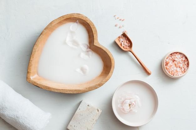 Ambiente de spa com tigela de leite de arroz, flores, sal, sabonete e toalha em fundo branco