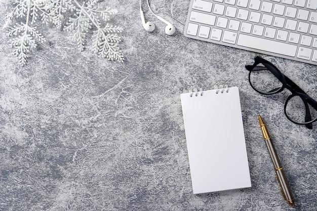 Ambiente de trabalho moderno em mesa de escritório branca com lápis de bloco de notas de computador folha verde