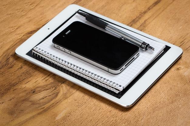 Ambiente de trabalho. telefone, tablet e bloco de notas na mesa