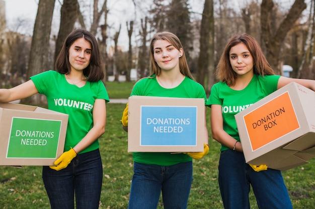 Ambiente e conceito de voluntariado com mulheres segurando caixas para doações